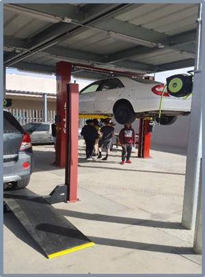 Car on lift in shop